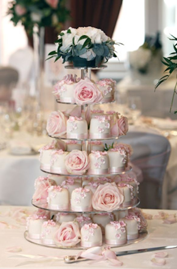 Weddbook ♥ Multi tier pink wedding cake and cupcakes to make your wedding special! These light pink cupcakes are in the shape of roses that look adorable. At th